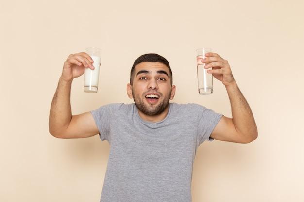 Вид спереди молодого мужчины в серой футболке, держащего стакан водяного молока на бежевом