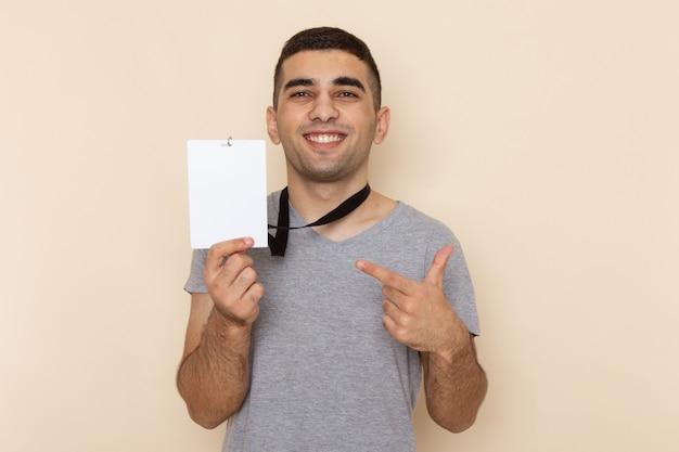 Вид спереди молодой мужчина в серой футболке, держащий удостоверение личности с улыбкой на бежевом