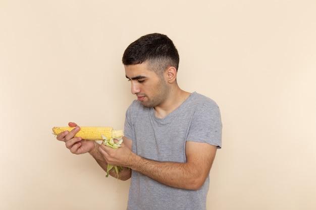 ベージュに生のトウモロコシを保持している灰色のtシャツの正面の若い男性