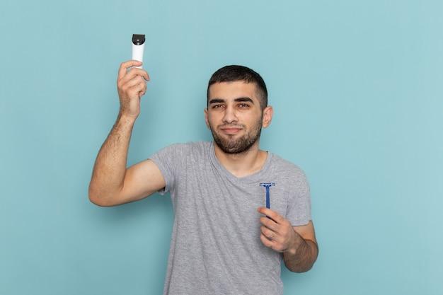 青にかみそりと電気かみそりを保持している灰色のtシャツの正面図若い男性