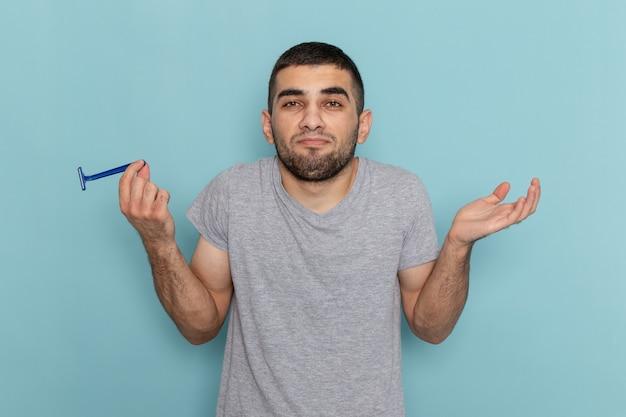 Вид спереди молодой мужчина в серой футболке, держащий бритву, позирует на синей бороде для бритья, цвет мужской пены для волос