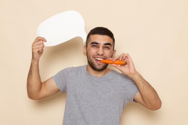 Вид спереди молодой самец в серой футболке с белым знаком и ест морковь на бежевом