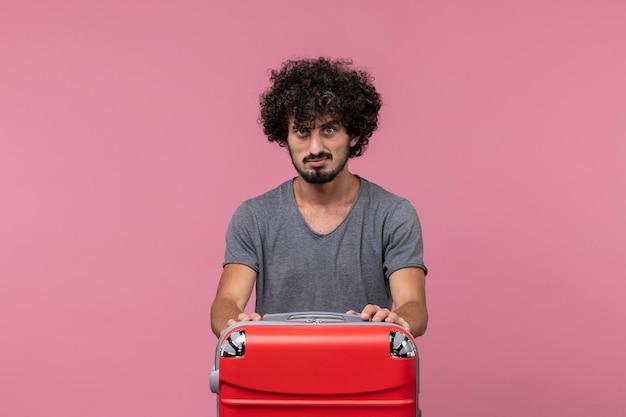 淡いピンクの空間での旅行の準備をしている灰色のtシャツの正面図若い男性