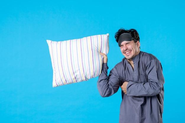 正面図青い背景色の枕を保持している彼のパジャマの若い男性人間の悪夢の休息夢の夜睡眠ベッドウェイク