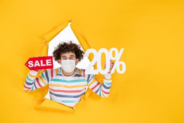 노란색 판매 코로나바이러스 건강 covid- 사진 전염병에 대한 마스크를 들고 판매 글을 쓰는 전면 보기 젊은 남성