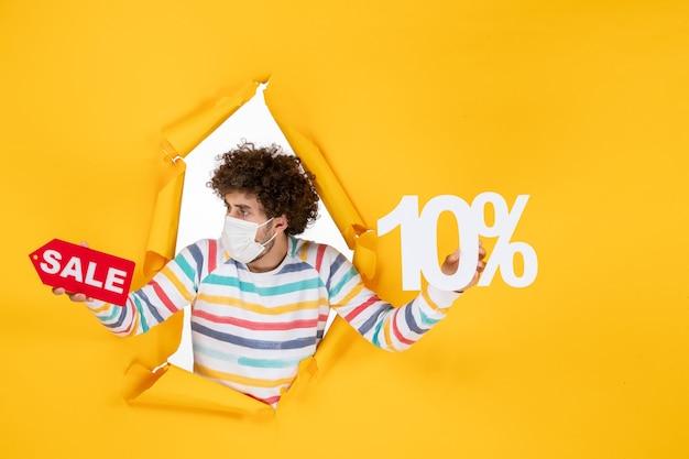 Вид спереди молодой мужчина в маске, держащий и продающий, пишущий на желтой фотографии, здоровье, пандемия коронавируса, распродажа цветов