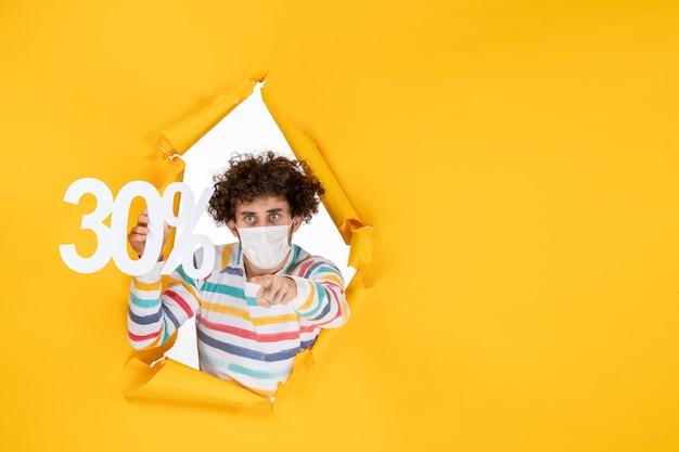 Вид спереди молодой самец в маске, держащийся за покупок желтого цвета, продажа пандемического вируса covid- фото