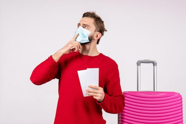 Вид спереди молодой мужчина в маске, держащий билеты на белой стене, путешествие, поездка, полет, отпуск, вирус, цветная эмоция