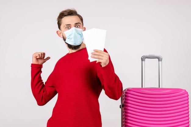 흰 벽 covid- 비행 여행 휴가 바이러스 색상 감정에 티켓을 들고 마스크에 전면보기 젊은 남성