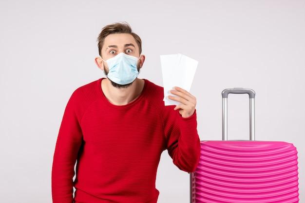 흰 벽 항해 covid- 비행 여행 휴가 바이러스 감정에 티켓을 들고 마스크에 전면보기 젊은 남성