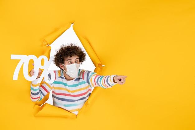 Вид спереди молодой самец в маске, держащий надпись на желтой распродаже, цветной вирус covid- фото, пандемия здоровья, покупки