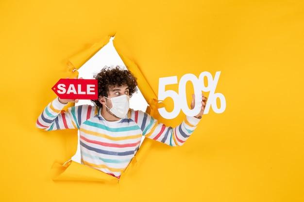 Вид спереди молодой самец в маске, держащий письмо на желтых покупках, продажа фотографий covid- продажа вирусов цвет пандемии