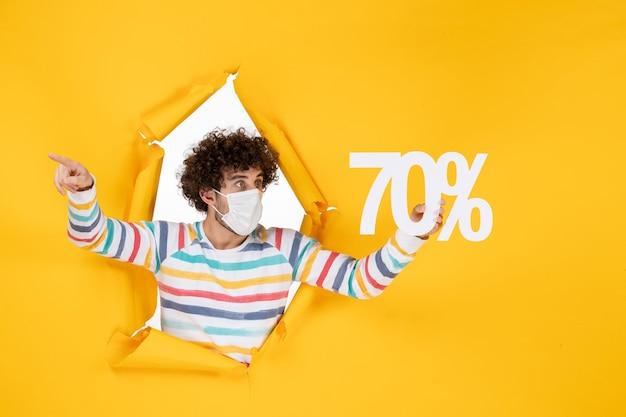 밝은 노란색 색상 판매 covid- 사진 쇼핑 바이러스에 글을 들고 마스크에 전면 보기 젊은 남성