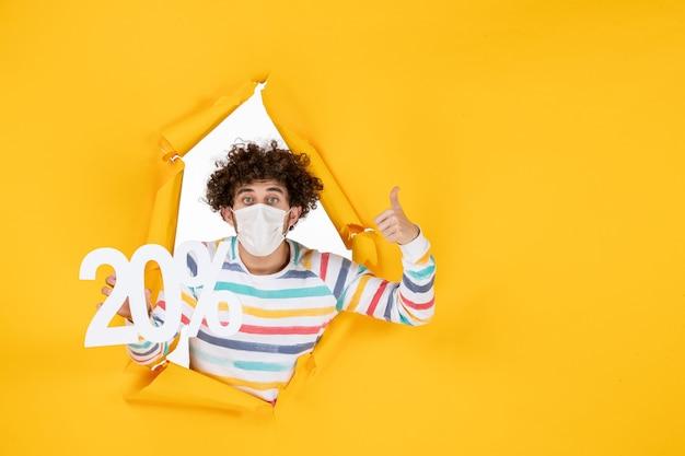 Вид спереди молодого мужчины в маске, держащего надпись на желтом пандемическом коронавирусе, фото здоровье covid- sale color
