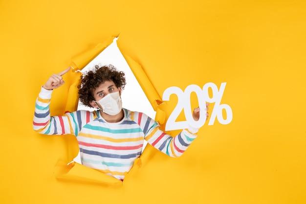 노란색 코로나바이러스 건강 covid-판매 컬러 사진에 글을 쓰고 있는 마스크를 쓴 전면 보기 젊은 남성