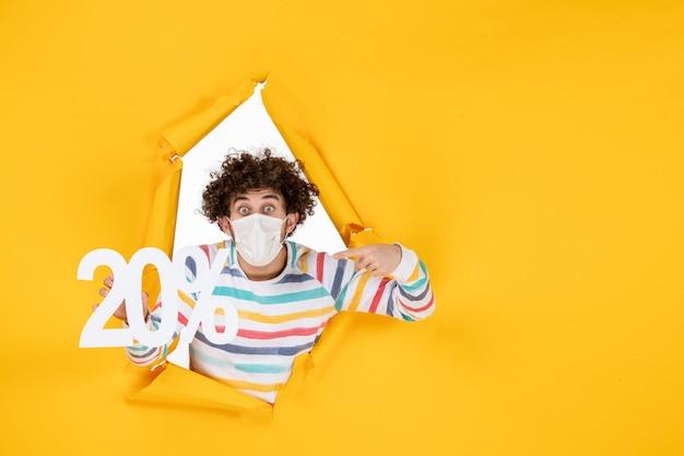 노란색 코로나바이러스 전염병 사진 건강 covid-판매 색상에 대한 글을 들고 마스크를 쓴 전면 보기 젊은 남성