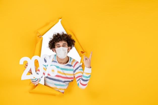 노란색 코로나바이러스 전염병 사진 건강 covid 판매 색상에 대한 글을 들고 마스크를 쓴 전면 보기 젊은 남성