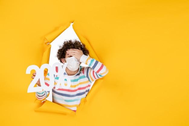 노란색 코로나바이러스 사진 건강 covid-판매 색상에 글을 쓰고 있는 마스크를 쓴 전면 보기 젊은 남성