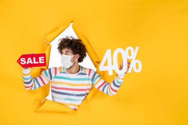 黄色の健康パンデミックショッピングcovid-ウイルス写真販売色に書き込みを保持しているマスクの若い男性の正面図 無料写真