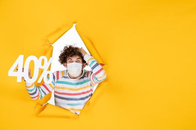 Вид спереди молодой мужчина в маске, держащий надпись на желтом вирусе здоровья, пандемическом шоппинге covid - цвет фото