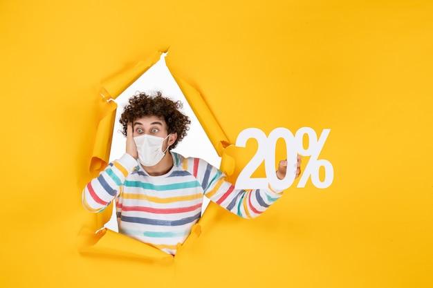 Вид спереди молодой мужчина в маске, держащий надпись на желтой распродаже, пандемия коронавируса, здоровье, covid - цветные фотографии
