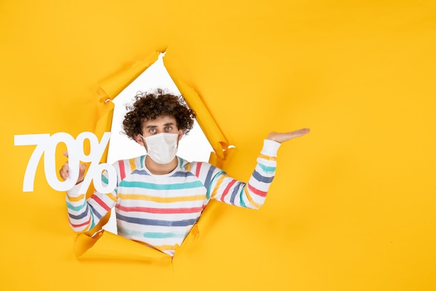 Вид спереди молодой самец в маске, держащий письмо на желтой распродаже, торговый цвет covid- пандемия здоровья