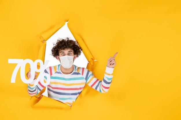 黄色のショッピングカラーcovid-写真ウイルス健康販売パンデミックに書き込みを保持しているマスクの正面図若い男性