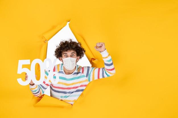 Вид спереди молодой самец в маске, держащий надпись на желтых покупках, фотографии пандемии коронавируса, цвет распродажи