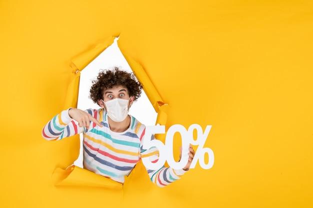 노란색 쇼핑 건강 전염병 covid-바이러스 사진 판매에 대한 글을 들고 마스크를 쓴 전면 보기 젊은 남성