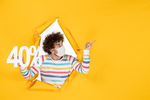 Вид спереди молодой самец в маске, держащий надпись на желтом вирусе, пандемическом шоппинге, цвет продаж covid
