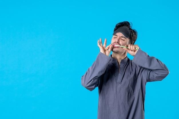 Вид спереди молодой мужчина в пижаме чистит зубы на синем фоне цвет кровать сон отдых ночь бодрствование темная подушка человек