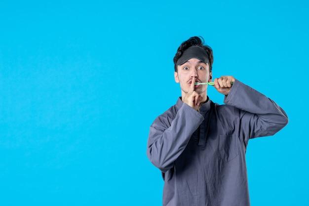 Вид спереди молодой мужчина в пижаме чистит зубы на синем фоне цвет постельный режим ночь бодрствование темная подушка кошмар сон человек