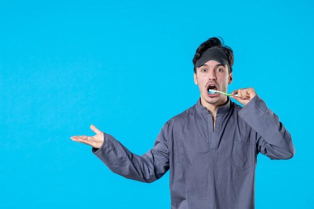 Вид спереди молодой мужчина в пижаме чистит зубы на синем фоне цвет отдых ночь бодрствование кошмар человеческая кровать темная подушка мечты