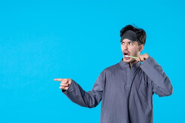 Вид спереди молодой мужчина в пижаме чистит зубы на синем фоне цвет отдыха ночь бодрствование сон кошмар кровать темная подушка