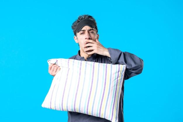 파란색 배경 색상 침실 휴식 불면증 수면 밤 침대 악몽 꿈 어두운 하품에 베개를 들고 잠옷에 젊은 남성