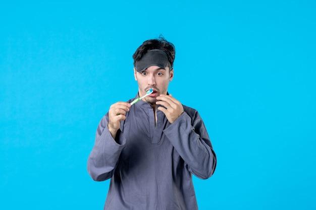 Вид спереди молодой мужчина в пижаме смотрит на зубную щетку с удивленным выражением лица на синем фоне сон кошмар ночь цвет просыпается чистой человеческой постели