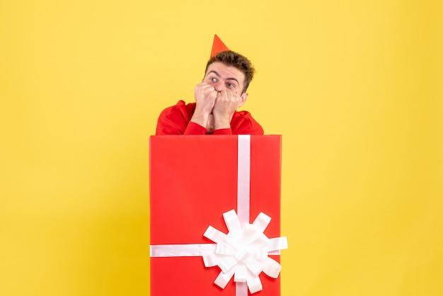 선물 상자 안에 빨간색 셔츠에 전면보기 젊은 남성