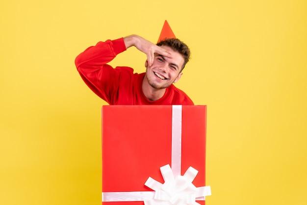 선물 상자 안에 앉아 빨간 셔츠에 전면보기 젊은 남성