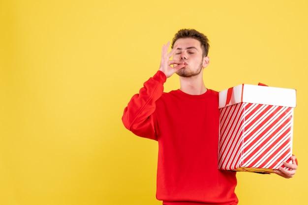 クリスマスプレゼントと赤いシャツの正面図若い男性