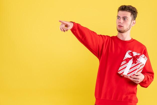 Вид спереди молодой самец в красной рубашке с рождественским подарком