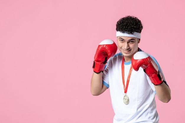 ピンクの壁にスポーツ服とボクシンググローブの正面図若い男性