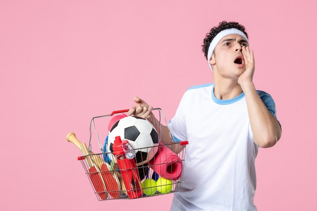 スポーツ物のピンクの壁でいっぱいのバスケットとスポーツ服を着た若い男性の正面図
