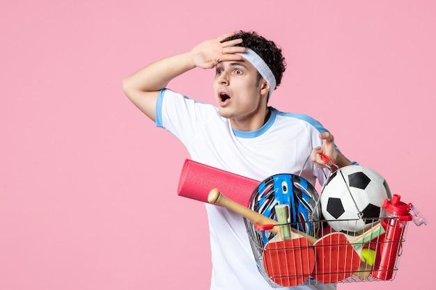 스포츠 것들 핑크 벽으로 가득한 바구니와 스포츠 옷 전면보기 젊은 남성