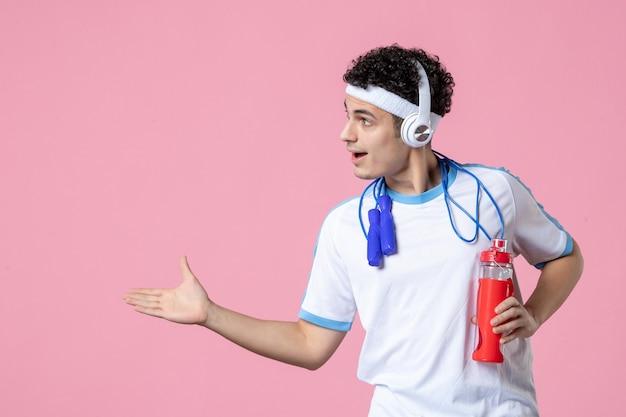 물 한 병 및 분홍색 벽에 밧줄을 건너 뛰는 스포츠 옷에 전면보기 젊은 남성