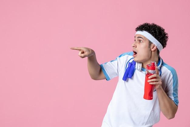 Вид спереди молодой мужчина в спортивной одежде со скакалкой и водной розовой стеной