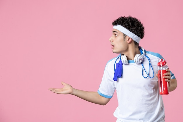 그의 목 핑크 벽 주위에 밧줄을 건너 뛰는 스포츠 옷 전면보기 젊은 남성