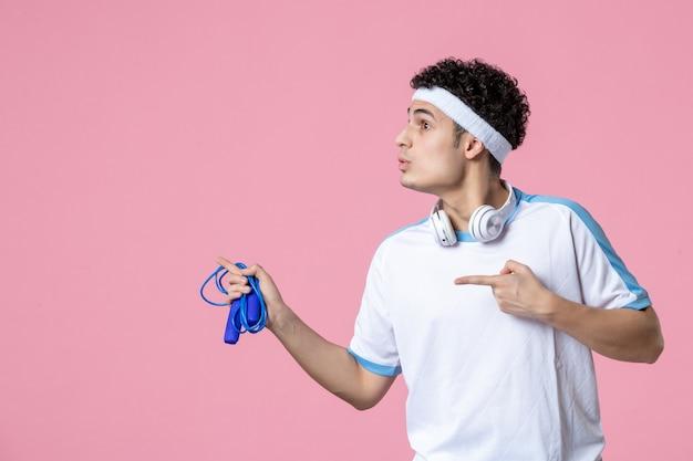 분홍색 벽에 밧줄을 건너 뛰는 스포츠 옷 전면보기 젊은 남성