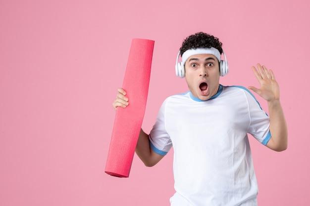 분홍색 벽에 요가 매트와 헤드폰 스포츠 옷 전면보기 젊은 남성