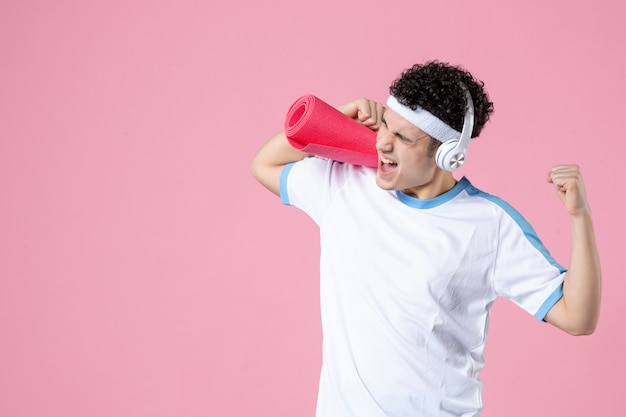 ピンクの壁にヨガマットとスポーツ服を着た若い男性の正面図