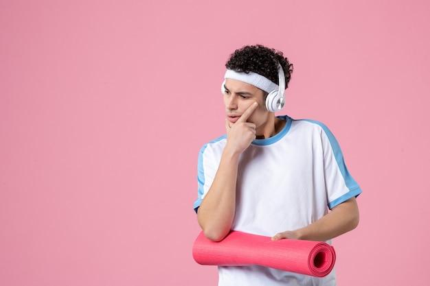 Вид спереди молодой мужчина в спортивной одежде с ковриком для йоги на розовой стене